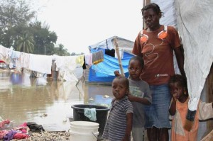 Velia Dorce with her children stand outside their tent flooded by Hurricane Tomas. ACT Alliance members are supporting people during this new emergency. Arne Grieg Riisnaes/NCA/ACT
