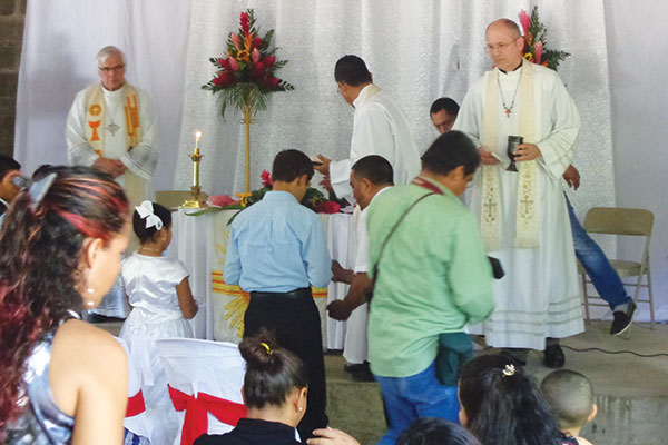 Rev. Robert Krestick (Redeemer, Waterloo, Ontario) and Rev. Richard Frey (St. Paul's, Elmira, Ontario) distribute Holy Communion at the church dedication in Telica.  In the middle, turned away from the camera, is former Nicaraguan synodical president Rev. Luis Antonio Diaz Turcio.
