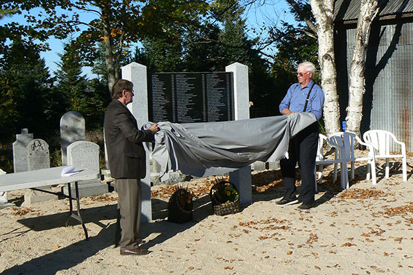 Bowman Mayor Michel David (right) and St. Paul's church member Stanley Cheslock unveil a monument honouring the 96 people buried on Cemetery Island.