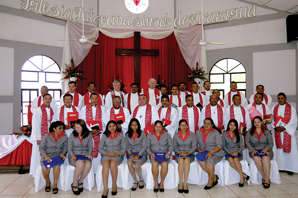 Newly consecrated deaconesses (front row) and newly ordained pastors (middle row) pose for a picture following the service. In the back row are pastors who took part in the service, including Rev. Ed Auger, ILSN President Marvin Donaire, and LCC President Emeritus Ralph Mayan (left to right, beneath the cross).