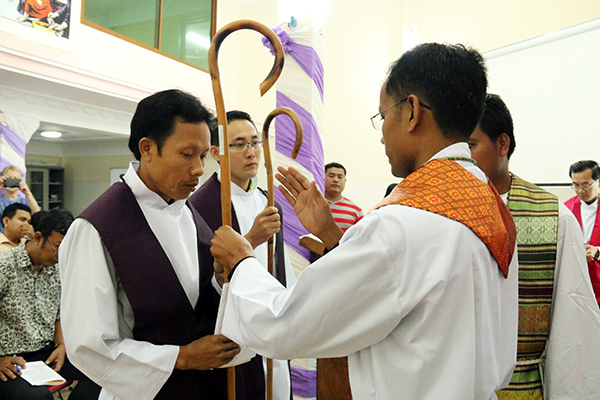 The newly ordained pastors are presented with shepherds' crooks by ELCC President Vannarith Chhim.