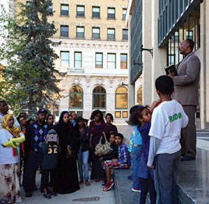 Rev. Asefa Aredo (far right) addresses the Oromo community during a candlelight vigil at Winnipeg's City Hall.
