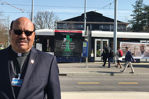 "Rev. James Luke poses in front of a street car bearing a sign promoting the ""Christians in Pakistan Under Threat"" event."